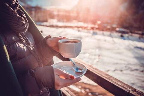 Organic Loose Tea - Woman holding hot tea looking outside at Winter landscape